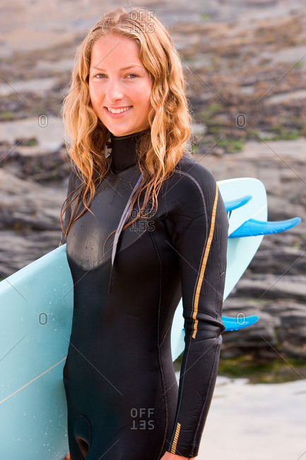 Woman standing with surfboard smiling