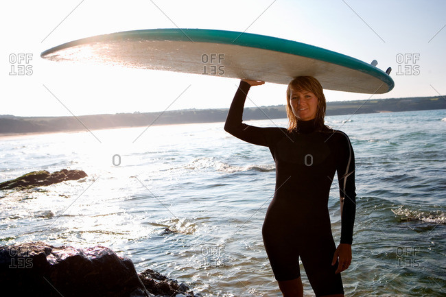 Woman standing with a surfboard