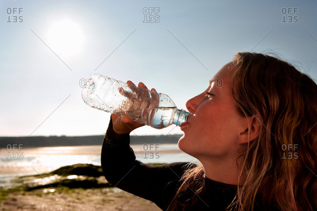 Woman drinking water in wetsuit