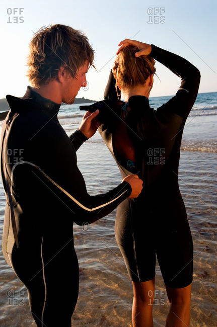 Man zipping up woman's wetsuit