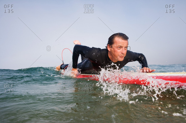 Man lying on surfboard in the water