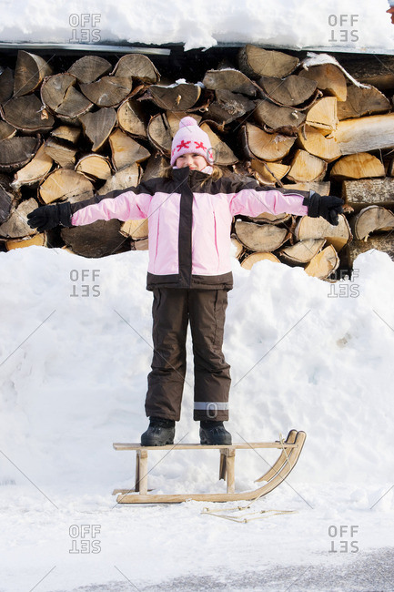 Young girl standing on sledge