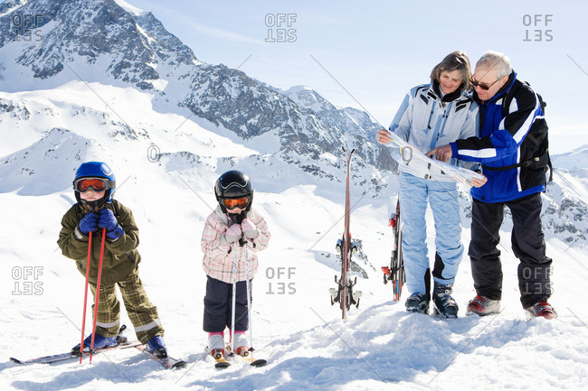 Grandparents reading piste map with kids
