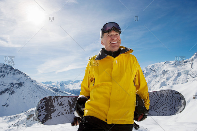 Mature male snowboarder with snowboard
