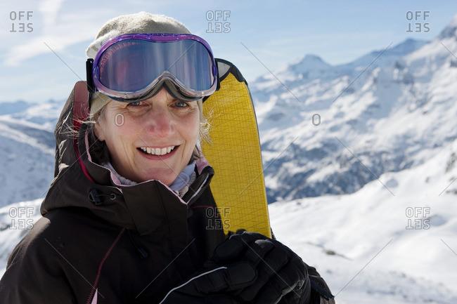 Mature female skier holding Skis