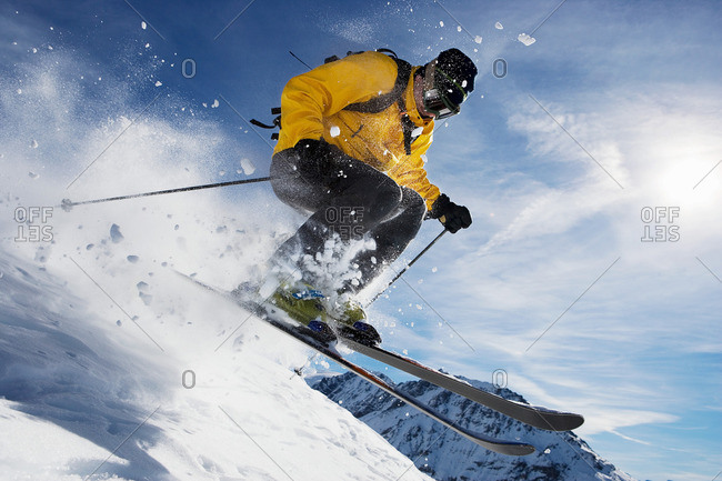 Male skiing over mountain ridge