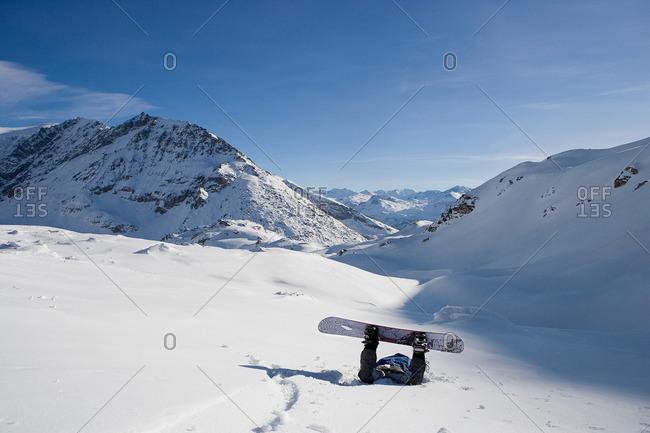 Fallen male snowboarder lying face down