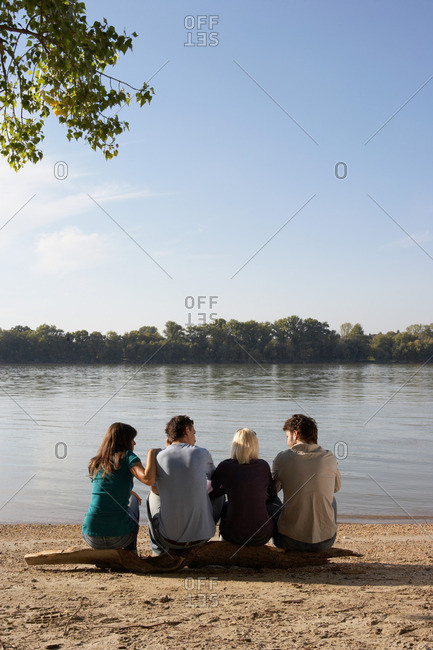 Four friends sitting on log by a lake