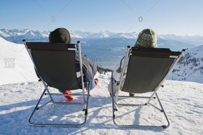 Man, woman relax on deck chairs in snow