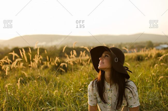 Woman wearing hat sitting in grass