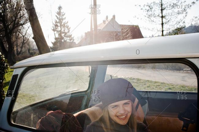 Girl smiling in back of car