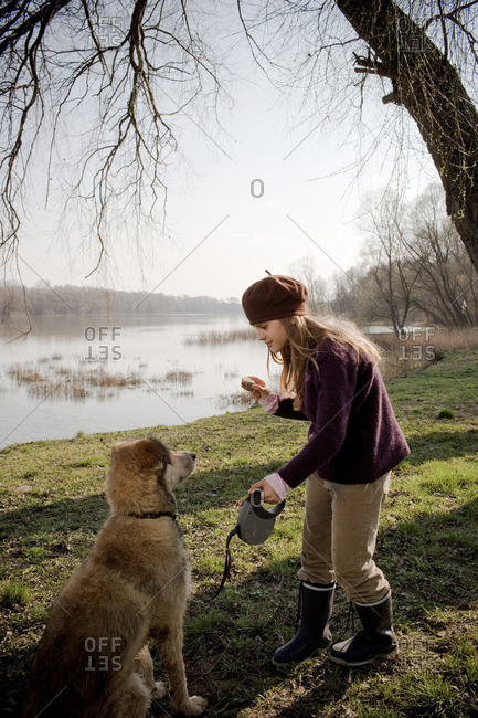 Girl by river holding cake with dog
