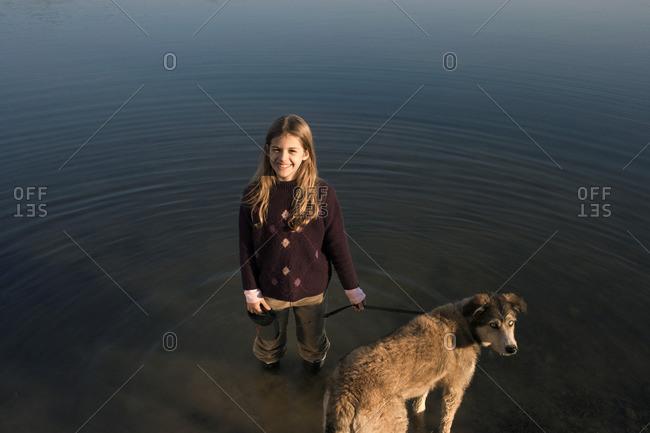 Girl standing in river holding dog