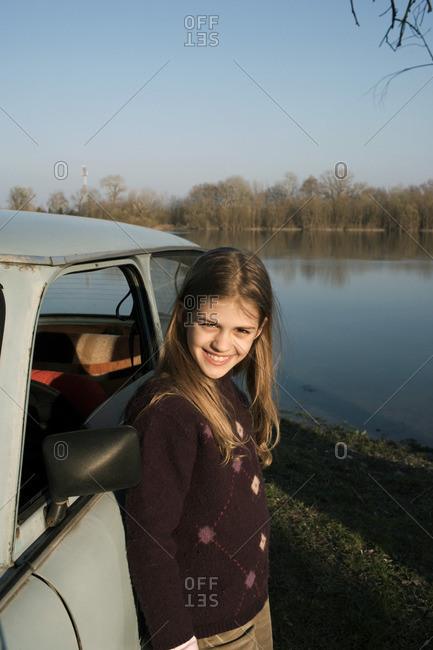 Girl standing by car on riverside
