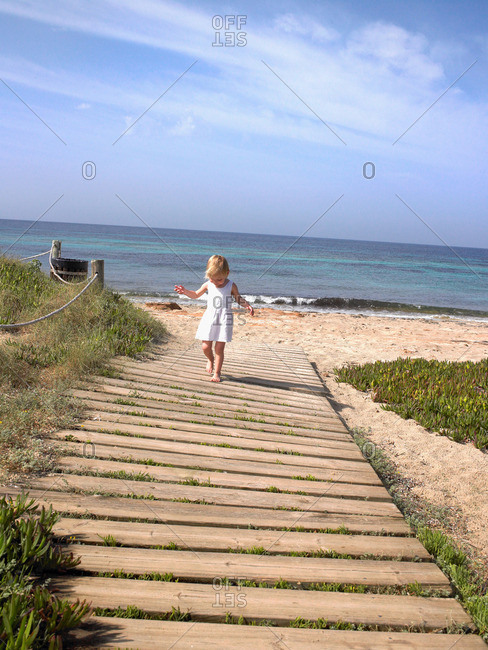 Young boy walking on a wooden path
