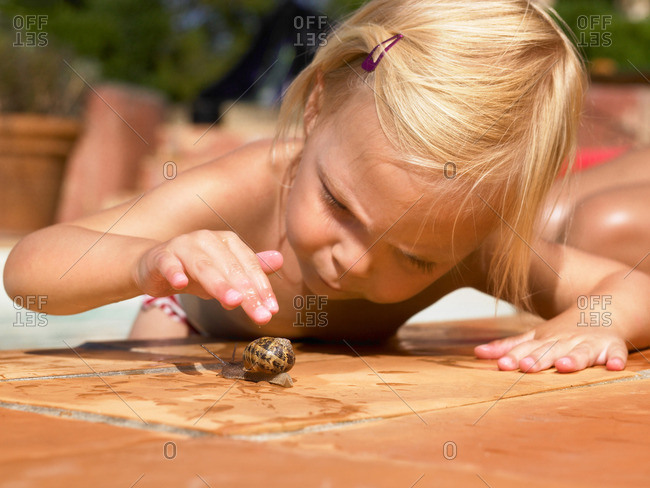 Little girl playing with a snail