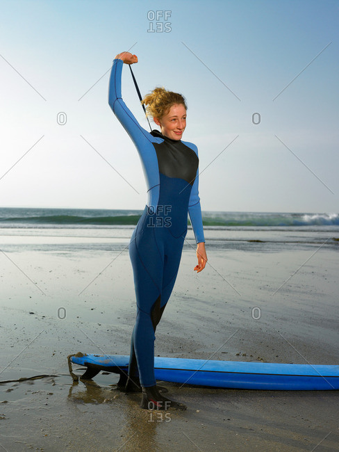 Female surfer standing on a beach