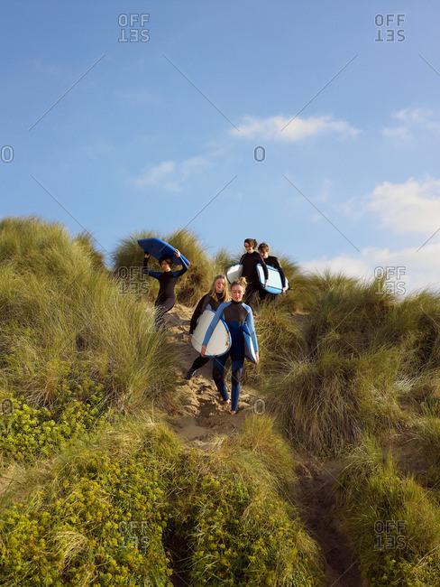 Five teenagers walking down a grass bank