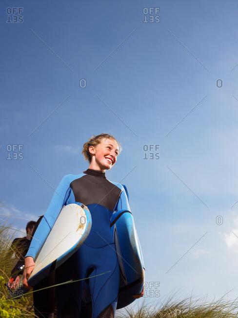 Female surfer walking through grass