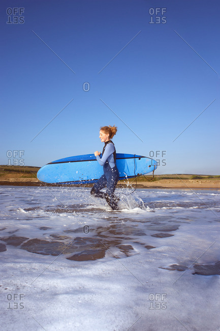 Female surfer running into the water