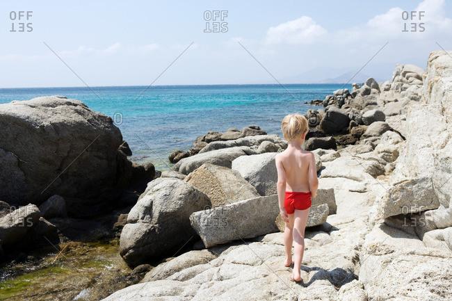 Young boy walking on rocks