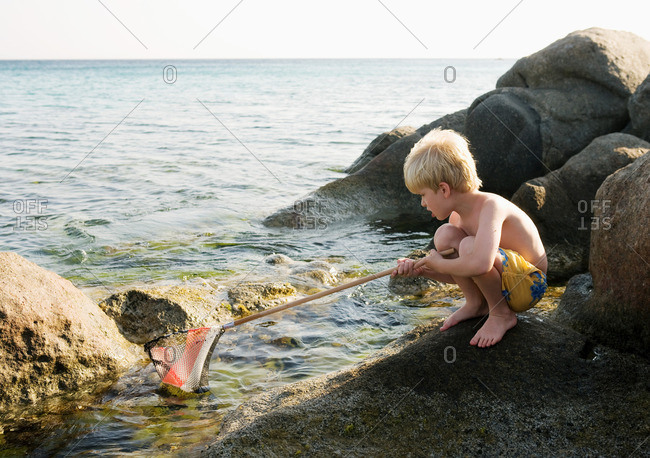 Young boy crouched on rocks fishing
