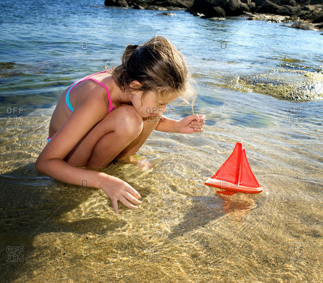 Young girl with a toy sailboat