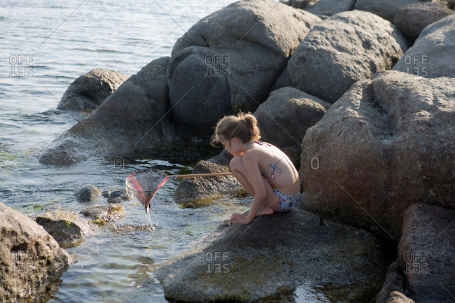 Young girl crouched on rocks fishing