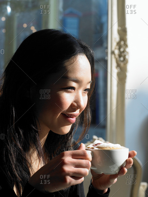 Young woman holding cappuccino smiling