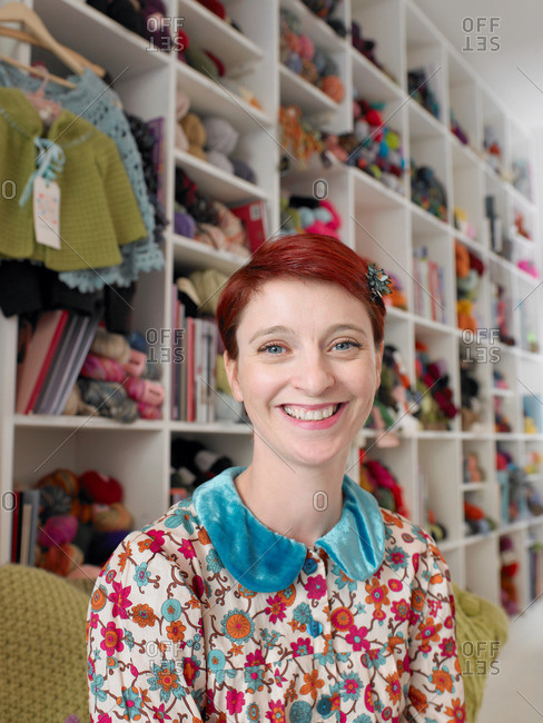 Woman sitting in craft shop smiling