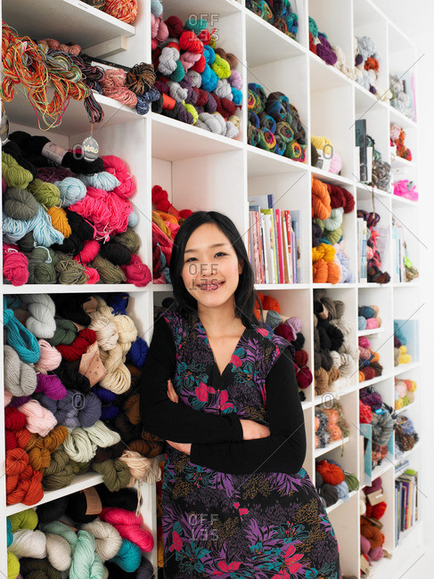 Young woman leaning on shelves of wool