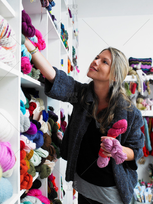 Young woman choosing wool in craft shop