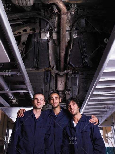 Three mechanics standing under a car