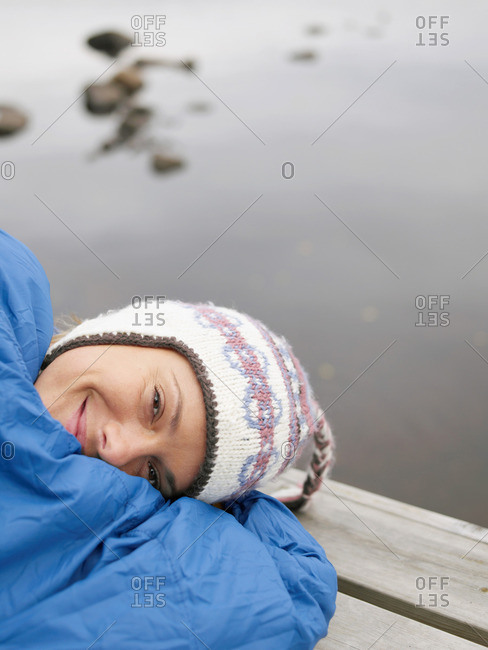 Woman with on a dock in a sleeping bag