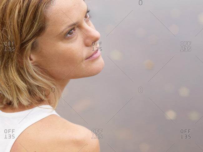 Woman sitting by the water looking up