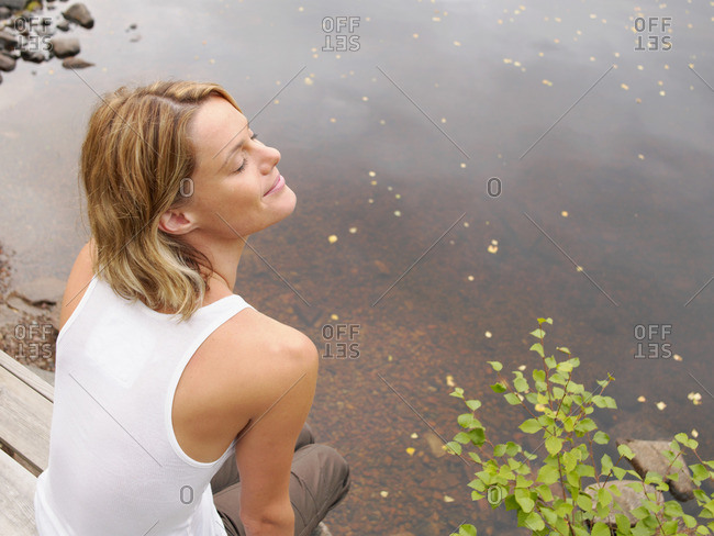 Woman sitting on dock with eyes closed