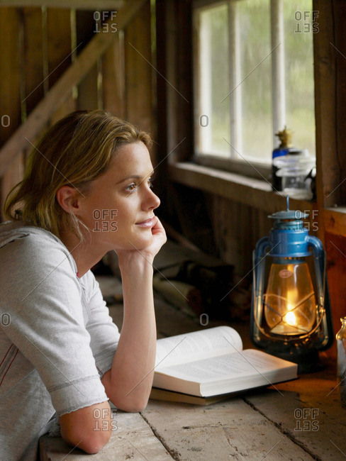 Woman sitting at a table in cabin with book.