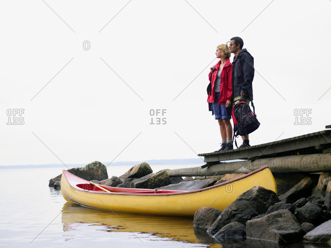 Couple standing on a dock near a boat