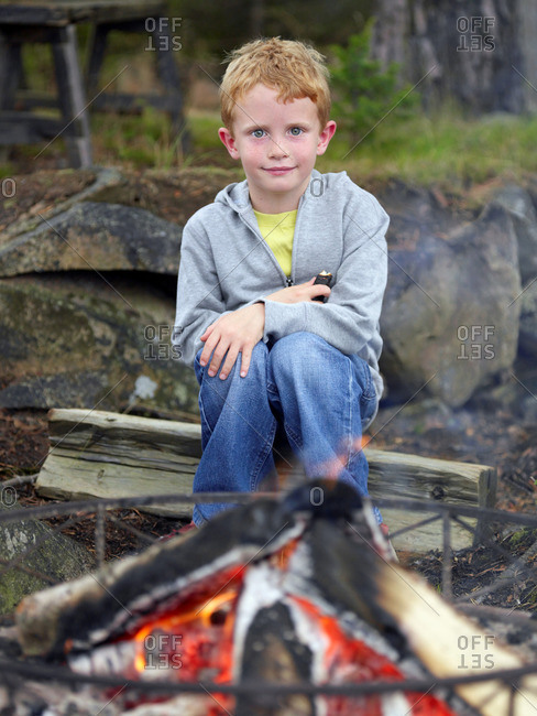 Young boy sitting by fire pit