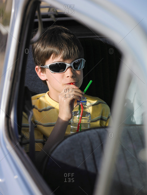 Boy in sunglasses sitting in car