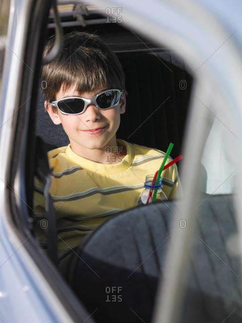 Boy in sunglasses sitting in car