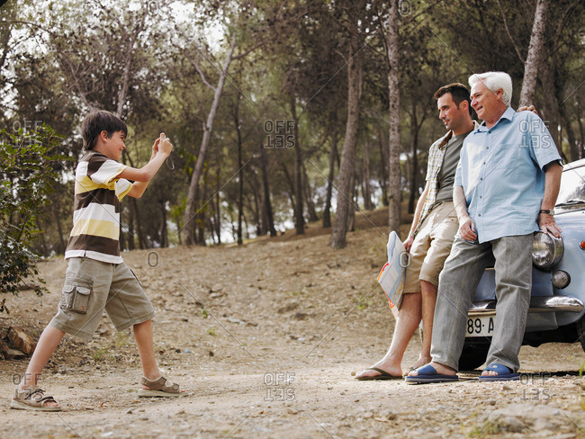 Boy photographing father and grandfather