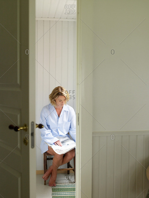 Woman on chair with a newspaper