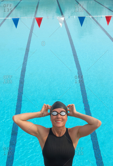 Female swimmer adjusting goggles by pool