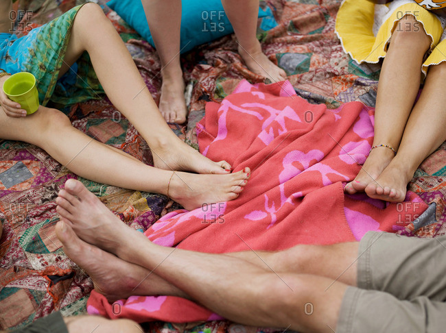 Four pair of bare feet on blankets