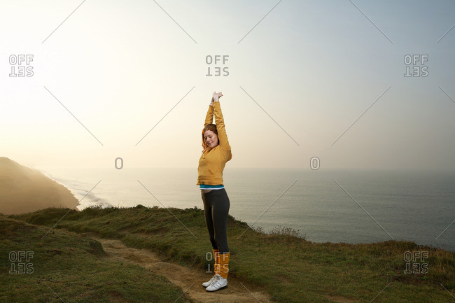 A woman stretching next to a cliff path
