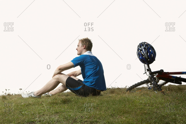 A male cyclist rests on a mountain path
