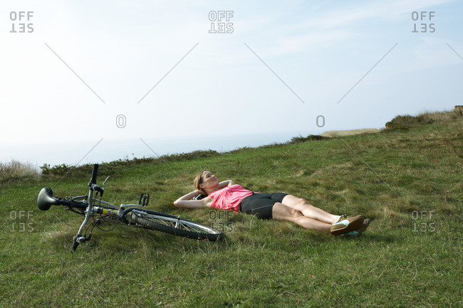 A woman rests on grass by her Bicycle