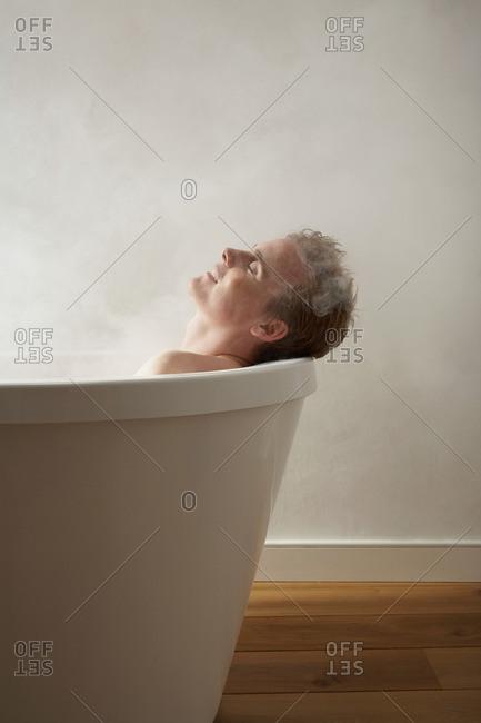 Mans head on edge of bath