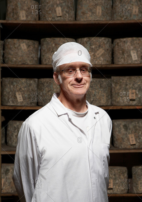 Man standing by line of cheeses.